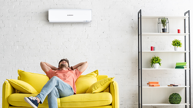 man sitting on couch underneath mistsubishi heavy industies air conditioner