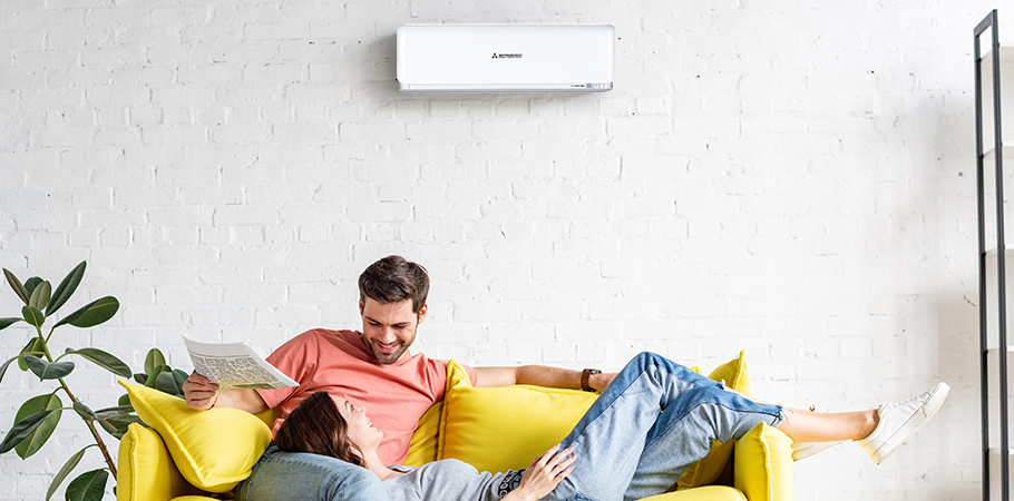 couple sitting on lounge underneath mitsubishi heavy industries split system air conditioner