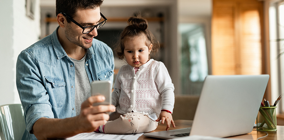 dad working from home inside with his daughter on table showing her phone
